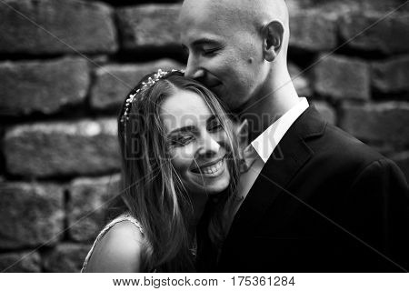 Smiling Groom Kisses Bride's Head Tenderly While She Leans To Him