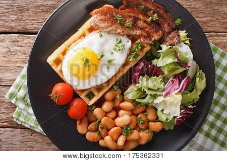 Hearty Breakfast With Fried Egg, Waffles, Bacon, Mix Salad And Beans Close-up. Horizontal Top View