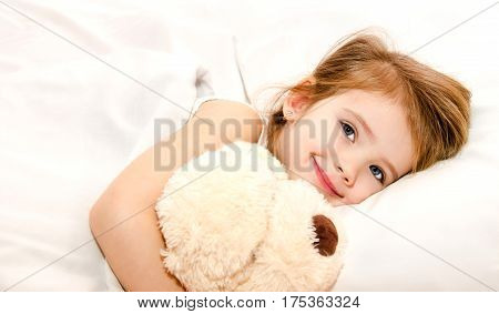 Adorable little girl in the bed with her toy