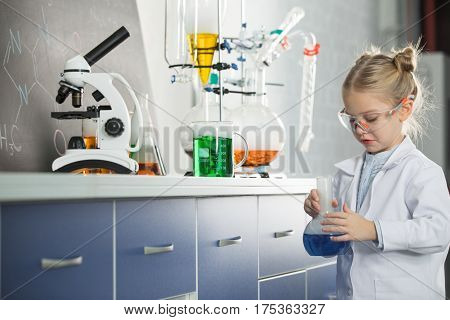 Little girl wearing lab coat and protective glasses holding flask with blue reagent