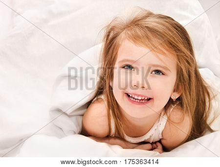 Happy adorable little girl awaked up in her bed