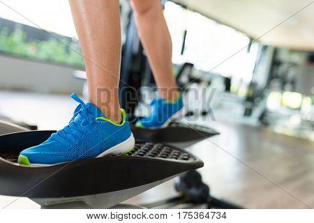 Woman step on Elliptical machine