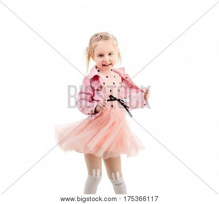 Adorable child in lovely pink dress dancing and spinning around, isolated on white background