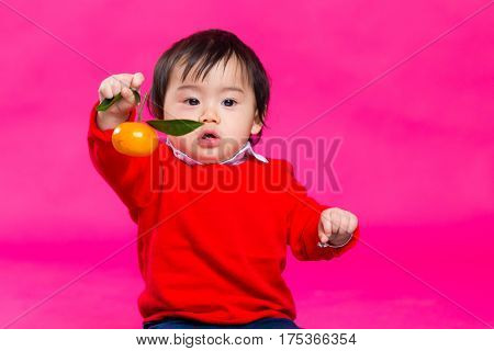 Asian baby boy holding a tangerine for lunar new year