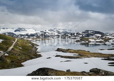 Beautiful norwegian landscape with high mountain plateau, lake, snow and road in the rocks. County Road 55, Sognefjellet, Norway.