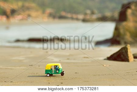 Tiny model of auto rickshaw moves across a sandy Goa beach in India