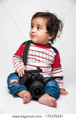 Indian baby boy photographer or infant or toddler holding a digital camera or dslr over white background and looking at camera with smile