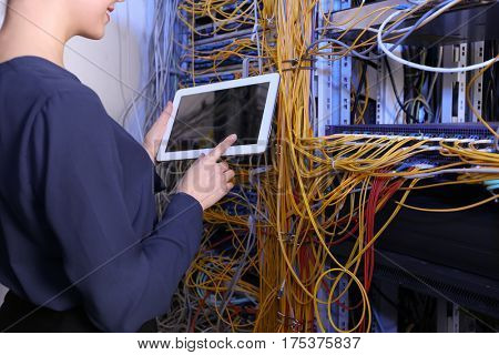 Beautiful young engineer with tablet computer in server room