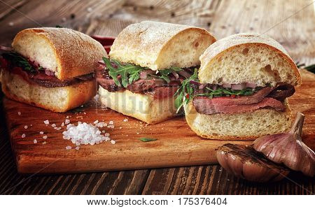 Sandwich With Beef Steak On A Wooden Stand.