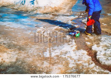little boy playing with paper boats in spring water puddle