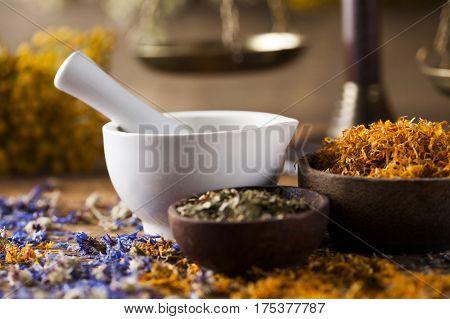 Herbs medicine,Natural remedy and mortar on vintage wooden desk background