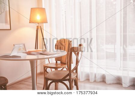 Table with chairs in light room interior