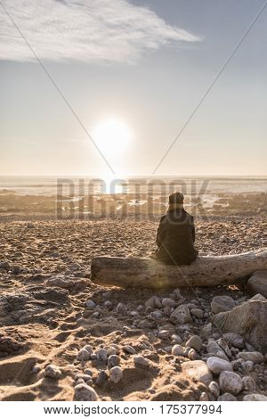 Woman sitting on driftwood in front of the sea (Les Sables d'Olonne, France)