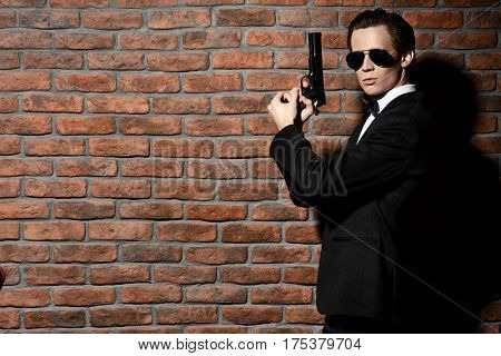 Handsome man in black suit and sunglasses holding a gun. Secret agent, mafia.
