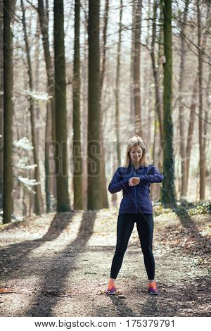 Trail running runner looking at heart rate monitor watch running in forest wearing warm jacket sportswear. Female jogger running training in woods.