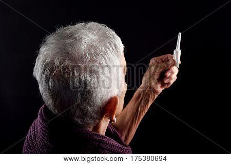 Senior woman Laxative on a black background