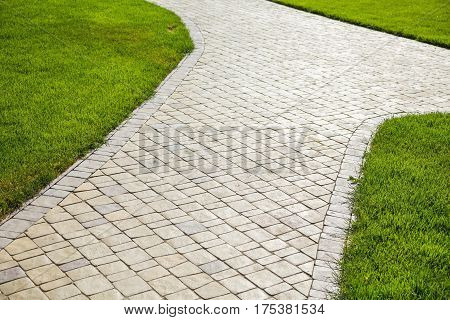 Sidewalk made from pavers running through a lawn