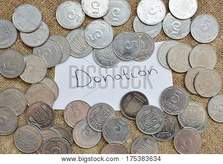 A Lot Of Coins Lying On The Background Of Burlap With A Label With The Words For A Donation. Ukraini