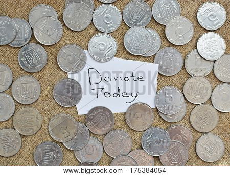 A Lot Of Coins Lying On The Background Of Burlap With A Label With The Words For A Donation Today. U