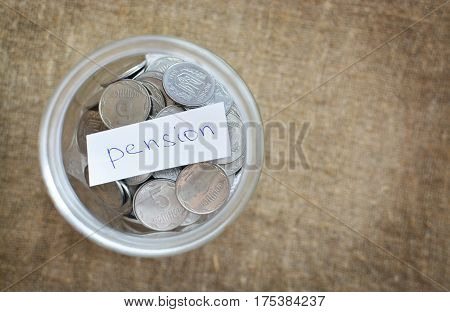 Glass Jar Filled With Coins Labeled With The Words Of The Pension. View From Above. Background Of Bu