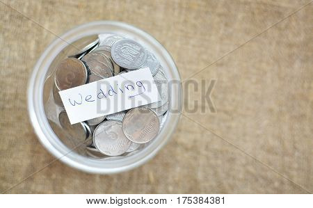 Glass Jar Filled With Coins Labeled With The Words Wedding. View From Above. Background Of Burlap. T