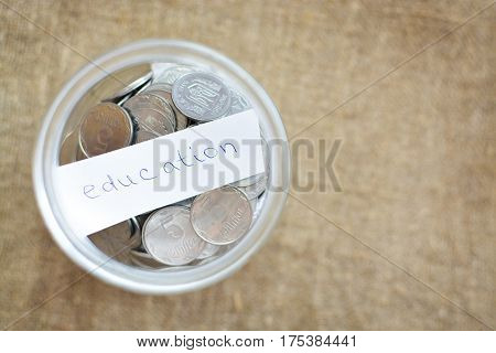 Glass Jar Filled With Coins Labeled With The Words Education. View From Above. Background Of Burlap.