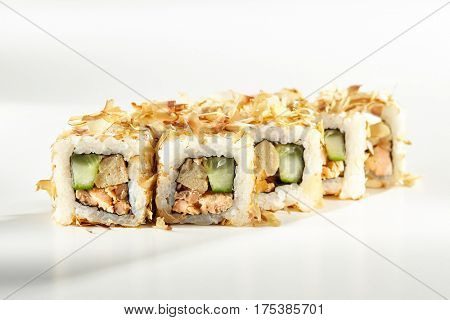 Japanese Sushi Food - Sushi Roll with Fried Salmon, Cucumber and Cream Cheese inside. Dried Shaved Bonito outside. Maki Sushi on White Background
