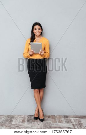 Full length portrait of a confident young business woman holding digital tablet while standing against gray background
