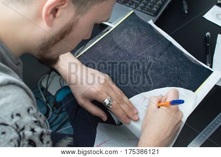 Making A Close-up Tattoo. An Artist With A Beard Draws A Sketch Of A Tattoo At His Workplace. View F