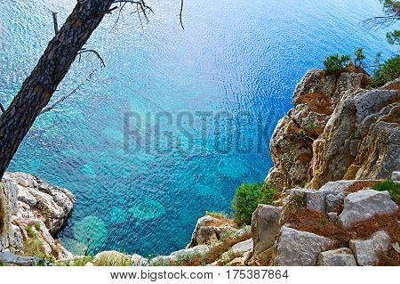 The rock is surrounded by water and sea waves beating against the rock. Adriatic sea is color blue. Nature of Montenegro