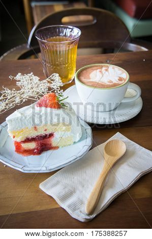 coffee cup and delicious cake strawberry and relax time moblie on table in coffee shop