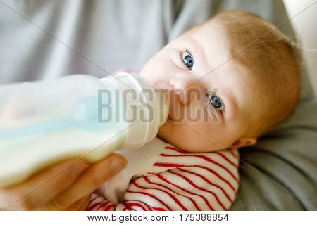 Mother feeding newborn baby daughter with milk in nursing bottle. Formula drink for babies. New born child, little girl laying in bed. Family, new life, childhood, beginning, bottle-feeding concept.