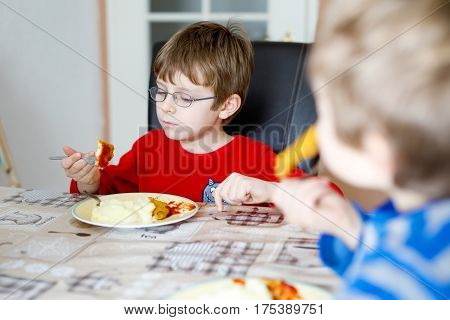 Two little school boys eating potato mash and chicken breast indoor. Blond children in domestic kitchen or in school canteen Cute kids and healthy food