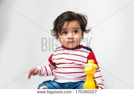 indian or asian small baby playing with toys or blocks over white background, toddler playing with toys, isolated and selective focus