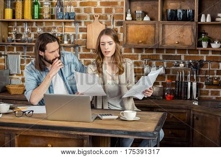 Young couple of freelancers working at home with laptop and documents