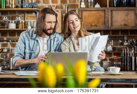Young couple of freelancers using laptop and looking at documents