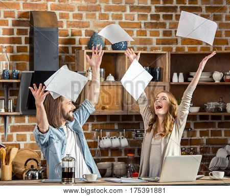 Excited young couple throwing documents while sitting and working with laptop
