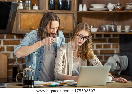 Young couple using laptop and drinking coffee while working together at home