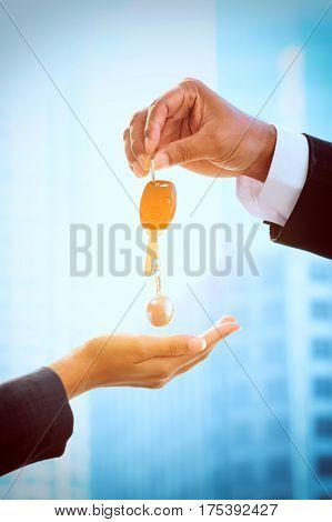 hands of car dealer giving keys to businessman