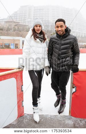 Beautiful young couple standing and holding hands at outdoor skating rink