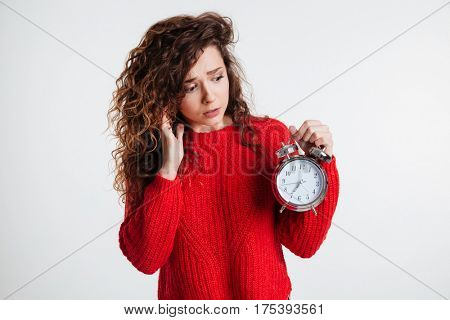 Portrait of a young upset woman with curly hair holding alarm clock over white background