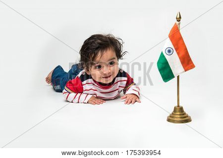 Cute baby boy on white background with indian flag or tricolour