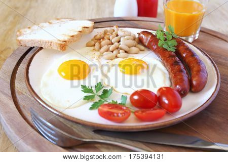 English breakfast with sausage fried egg baked beans and orange juice
