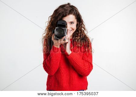 Portrait of a young smiling woman filming with retro camera isolated on the white background