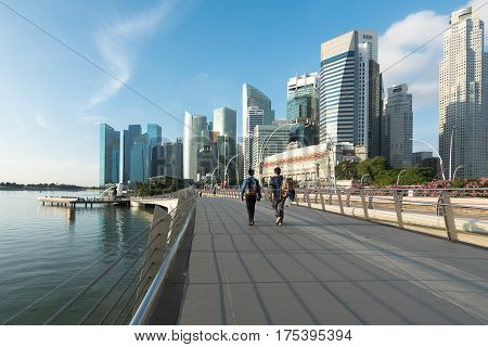 Pedestrians walk along bridge near Marina bay in Singapore with Singapore skyscraper and Merlion park in background.