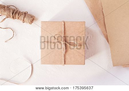 Gift packing process with vintage box and brown paper on light background