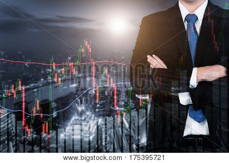 Double exposure of Businessman and trading stock market graph and bar on city at night. Business financial and trading concept.