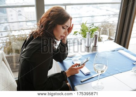 Side view of Displeased Woman in dress which sitting by the table in restaurant and using phone