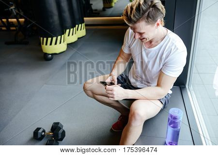 Side view of muscular man which using smartphone and sitting near window in gym