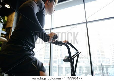 Side view of Muscular man which using spinning bicycle in gym near the window